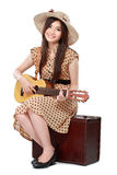 Frau, die auf ihrem Koffer beim Spielen der Gitarre sitzt Stockfotos