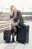 Frau, die auf ihrem Koffer an der Bahnstation sitzt Stockfoto