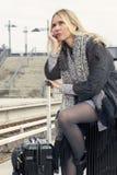 Frau, die auf ihrem Koffer an der Bahnstation sitzt Stockfotos