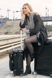 Frau, die auf ihrem Koffer an der Bahnstation sitzt Stockfotografie
