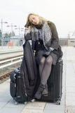 Frau, die auf ihrem Koffer an der Bahnstation sitzt Lizenzfreie Stockfotos