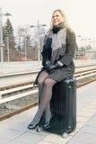 Frau, die auf ihrem Koffer an der Bahnstation sitzt Stockbilder