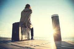 Frau, die auf ihrem Koffer wartet auf den Sonnenuntergang sitzt Lizenzfreie Stockbilder