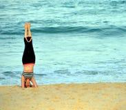 Frau, die auf ihrem Kopf steht und Yoga auf dem Strand tut Lizenzfreies Stockbild