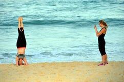 Frau, die auf ihrem Kopf steht und Yoga auf dem Strand tut Lizenzfreies Stockfoto