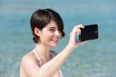 Frau, die auf ihrem Mobile sich fotografiert Lizenzfreie Stockbilder