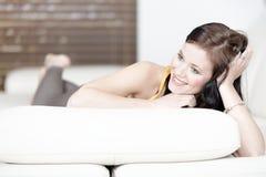 Frau, die auf ihrem Sofa sich entspannt Lizenzfreie Stockfotografie