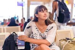 Frau, die auf ihren Flug wartend sitzt Stockbilder
