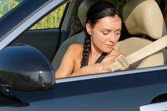 Frau, die auf ihren Sicherheitsgurt sich setzt Lizenzfreie Stockbilder
