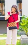 Frau, die auf ihrer Tasche sucht Lizenzfreie Stockbilder