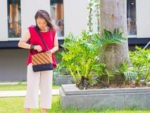 Frau, die auf ihrer Tasche sucht Lizenzfreie Stockfotografie