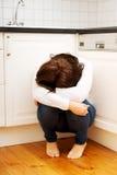 Frau, die auf Küchenboden in der Krise sitzt Stockbilder