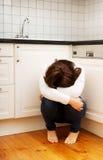 Frau, die auf Küchenboden in der Krise sitzt Stockfotografie