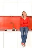 Frau, die auf Küchezählwerk sitzt Lizenzfreies Stockfoto