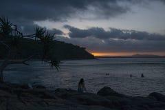 Frau, die auf Küste am bewölkten Abend sitzt stockfotografie