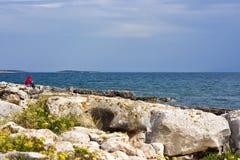 Frau, die auf Küste sitzt Stockfoto