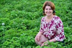 Frau, die auf Kartoffelacker im Sommer sitzt lizenzfreie stockfotos