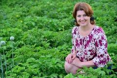 Frau, die auf Kartoffelacker im Sommer sitzt lizenzfreies stockbild