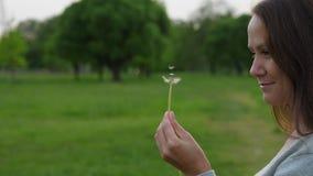 Frau, die auf kleinen Samen auf Löwenzahnkopf schaut stock video footage