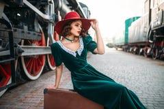 Frau, die auf Koffer gegen Dampfzug sitzt Stockfotografie