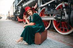 Frau, die auf Koffer gegen Dampfzug sitzt Stockfotos