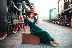 Frau, die auf Koffer gegen Dampfzug sitzt Lizenzfreie Stockfotografie