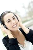 Frau, die auf Kopfhörer lächelt und hört Stockfoto