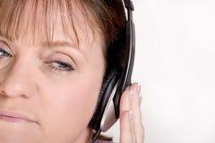 Frau, die auf Kopfhörern hört Stockbild