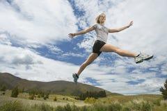 Frau, die auf ländliche Landschaft springt Lizenzfreies Stockbild