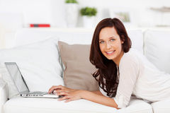 Frau, die auf Laptop grast Stockbilder