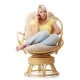 Frau, die auf Lehnsessel mit Handy sitzt Lizenzfreie Stockfotos