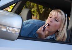 Frau, die auf Lippenstift beim Antreiben sich setzt lizenzfreies stockbild