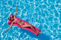 Frau, die auf Luftmatraze im Swimmingpool sich entspannt Stockbilder