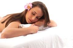 Frau, die auf Massage-Tabelle sich entspannt Stockfoto