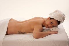 Frau, die auf Massage-Tabelle sich entspannt Stockfotografie