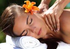 Frau, die auf Massagetabelle am Badekurort liegt Stockfoto