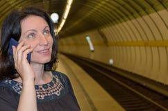 Frau, die auf Mobile in der U-Bahnstation spricht lizenzfreie stockfotografie