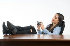 Frau, die auf Mobiltelefon im Büro, sitzend mit den Beinen auf d spielt stockfoto