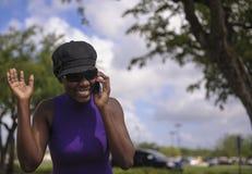 Frau, die auf Mobiltelefon lacht Lizenzfreies Stockfoto