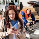 Frau, die auf Mobiltelefon nach Autozusammenbruch wählt stockfotografie