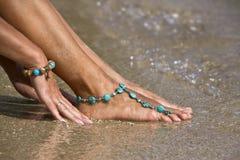 Frau, die auf nassem Sand mit Armbändern aufwirft Lizenzfreies Stockfoto