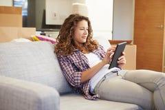 Frau, die auf neuem Haus Sofa With Digital Tablet Ins sich entspannt Stockbilder