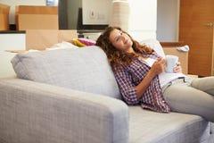 Frau, die auf neuem Haus Sofa With Hot Drink Ins sich entspannt Lizenzfreie Stockfotos