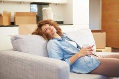 Frau, die auf neuem Haus Sofa With Hot Drink Ins sich entspannt Lizenzfreie Stockfotografie