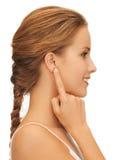 Frau, die auf Ohr zeigt stockbild