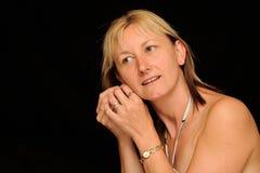 Frau, die auf Ohrring sich setzt Lizenzfreies Stockfoto