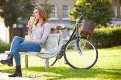 Frau, die auf Park-Bank mit Mitnehmerkaffee sich entspannt Lizenzfreie Stockfotos
