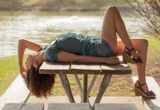 Frau, die auf Picknicktisch liegt Lizenzfreies Stockfoto
