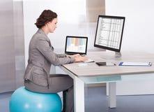 Frau, die auf pilates Ball unter Verwendung des Computers sitzt Stockbild