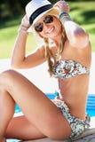 Frau, die auf Rand des Schwimmens im Pool sitzt Lizenzfreies Stockbild